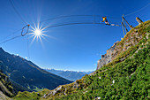 Woman on the Gemmi adventure via ferrata goes over rope bridge, Valais Alps in the background, Gemmi, Bernese Alps, Valais, Switzerland