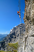 Woman climbs on overhanging ladder on adventure via ferrata Gemmi, Gemmi, Bernese Alps, Valais, Switzerland