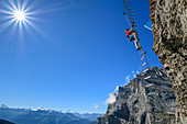 Woman climbs on overhanging ladder on adventure via ferrata Gemmi, Valais Alps in the background, Gemmi, Bernese Alps, Valais, Switzerland