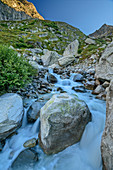 Mountain stream flows over large boulders, Baltschiedertal, Bernese Alps, Valais, Switzerland