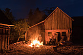 Campfire in front of old barn, Germany, Brandenburg, Spreewald
