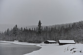 Two wooden huts by the lake in deep snow, Storjola, Borgafjäll, Lapland, Sweden