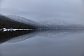Snow-capped mountains are reflected in a lake, Borgafjäll, Jämtland, Sweden