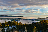View over mountains and a valley with fog in winter, Asele, Lapland, Sweden
