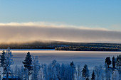 Wall of clouds and a view of a lake and snowy forest near Dorotea, Lapland, Sweden
