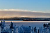 Wolkenwand und Blick auf einen See und verschneiten Wald bei Dorotea, Lappland, Schweden