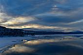 Winterstimmung mit leuchtenden Wolken an einem See in Lappland, Arjeplog, Schweden
