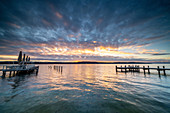 Sunrise on the promenade with bathing jetty on the north shore of Lake Starnberg, Starnberg, Bavaria, Germany.