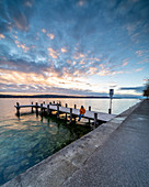 Sunrise on the promenade with bathing jetty on the north shore of Lake Starnberg, Starnberg, Bavaria, Germany.