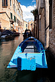 View of a blue boat along a canal, in the background Madonna dell'Orto, Cannaregio, Venice, Veneto, Italy, Europe