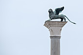 View of the Lion of St. Mark, the bronze statue the symbol of Venice perched on the column on St. Mark's Square, San Marco, Venice, Veneto, Italy, Europe