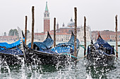View of the Venetian gondolas on St. Mark's Square with spray, in the background the island of San Giorgio, Venice, Veneto, Italy, Europe