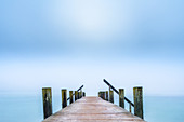 Jetty on Lake Starnberg in autumn morning fog, Garatshausen, Bavaria, Germany