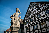 Fountain sculpture and half-timbered houses in the upper town of Mühlheim an der Donau, Baden-Württemberg, Germany