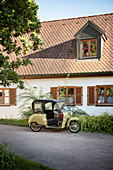 historic tricycle motorcycle in the alleys of the old town of Neuburg an der Donau, district of Neuburg-Schrobenhausen, Bavaria, Germany