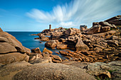 The mean Ruz lighthouse with the red rocks of the Cote de Granit Rose in the foreground, Brittany, France, Europe