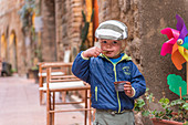 A young boy enjoys his chocolate ice cream in the alleys of San Gimignano, Province of Siena, Tuscany, Italy