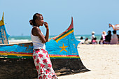 Young woman leaning on fishing boat on the beach at Morondava, Madagascar, Africa