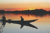 Gambia; Central River Region; Abendrot am Gambia-Fluss bei Kuntaur; zwei Männer sitzen in einem Boot in der Nähe des Ufers