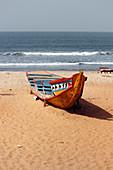 Gambia; Capital Region Banjul; Kotu Beach near Serekunda; brightly painted fishing boat on the beach