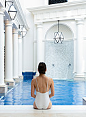 Woman in white bathing suit, sitting with her back to the camera, on the edge of an interior pool. Bath, United Kingdom