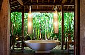 Freestanding bathtub inside an open bathroom in an old wooden house in Bali. Bali, Indonesia.