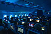 Passengers enjoy in-flight entertainment in Moana Economy Class on the Air Tahiti Nui Boeing 787 Dreamliner aircraft flying from Charles de Gaulle Airport in France to Los Angeles International Airport in the United States