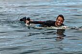 Ein Surfer paddelt im Wasser am Surfgebiet Teahupoo, Tahiti Iti, Tahiti, Windward Islands, Französisch-Polynesien, Südpazifik