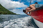 Smiling woman with camera leans over tour boat to photograph waves, Tahiti Iti, Tahiti, Windward Islands, French Polynesia, South Pacific