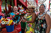 Three Tahitian women at a flower stand in the 'Marché Papeete' market hall, Papeete, Tahiti, Windward Islands, French Polynesia, South Pacific