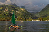 People enjoy a trip on an outrigger canoe with sails in front of a lush mountain backdrop, near Papeete, Tahiti, Windward Islands, French Polynesia, South Pacific