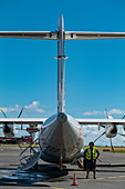 Ground worker stands at Air Tahiti ATR 72-600 aircraft on the apron of Tahiti Faa'a International Airport (PPT), Papeete, Tahiti, Windward Islands, French Polynesia, South Pacific