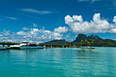Catamaran ferry Bora Bora Navettes at the pier of Bora Bora Airport (BOB) with turquoise lagoon water and Mount Otemanu in the distance, Bora Bora, Leeward Islands, French Polynesia, South Pacific