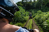 Looking over the shoulder during an excursion in a quad all-terrain vehicle on a dirt road through lush mountain vegetation, Bora Bora, Leeward Islands, French Polynesia, South Pacific