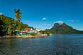 Native houses beside Bora Bora Lagoon with Mount Otemanu in the distance, Bora Bora, Leeward Islands, French Polynesia, South Pacific