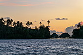 Silhouette of overwater bungalows along Bora Bora Lagoon at sunset, Bora Bora, Leeward Islands ,, French Polynesia, South Pacific