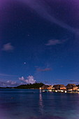 Overwater bungalows of the Sofitel Bora Bora Private Island Resort in the lagoon of Bora Bora with the Southern Cross in the starry sky at night, Bora Bora, Leeward Islands, French Polynesia, South Pacific