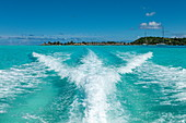 The waves of a speedboat in the turquoise waters of the Bora Bora lagoon with overwater bungalows in the distance, Bora Bora, Leeward Islands, French Polynesia, South Pacific