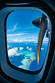 View out of window on engine of Air Tahiti ATR 72-600 airplane with view of Taha'a Island, Taha'a, Leeward Islands, French Polynesia, South Pacific