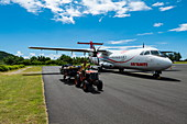 Tractor with luggage in front of Air Tahiti ATR 72-600 aircraft on apron at Moorea Airport (MOZ), Windward Islands, French Polynesia, South Pacific