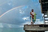 Tahitian woman on pier with rainbow behind, Moorea, Windward Islands, French Polynesia, South Pacific
