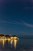 Overwater bungalows of the Sofitel Ia Ora Beach Resort in the lagoon of Moorea with the Southern Cross in the starry sky at night, Moorea, Windward Islands, French Polynesia, South Pacific