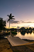 Hammock on the beach and overwater bungalows of the Sofitel Ia Ora Beach Resort in the Moorea Lagoon at daybreak, Moorea, Windward Islands, French Polynesia, South Pacific