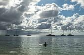 Silhouette eines Mannes im Wasser der Opunohu Bay mit Segelbooten vor Anker dahinter, Moorea, Windward Islands, Französisch-Polynesien, Südpazifik