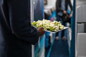Flight attendants with tray of fresh Tahitian tiare flowers greeting passengers on board Air Tahiti Nui Boeing 787 Dreamliner airplane, Paris Charles de Gaulle Airport (CDG), near Paris, France