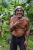 Cheeky Polynesian man near Afareaitu Waterfall, Moorea, Windward Islands, French Polynesia, South Pacific
