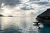 Cruise ship MS Astor (Transocean Cruises) leaves Opunohu Bay during a thunderstorm with overwater bungalows at the Hilton Moorea Lagoon Resort & Spa, Moorea,  Windward Islands, French Polynesia, South Pacific