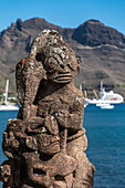 Detail of a tiki statue with passenger cargo ship Aranui 5 (Aranui Cruises) on pier in the distance, Taiohae, Nuku Hiva, Marquesas Islands, French Polynesia, South Pacific