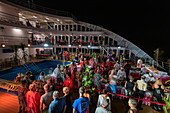 The passengers of the passenger cargo ship Aranui 5 (Aranui Cruises) enjoy a Polynesian evening with a rich buffet and cultural entertainment, at sea near the Marquesas Islands, French Polynesia, South Pacific