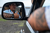Thumbs up: a man with tattoos on his arm looks in the rearview mirror of his four-wheel drive vehicle, Tekoapa, Ua Huka, Marquesas Islands, French Polynesia, South Pacific